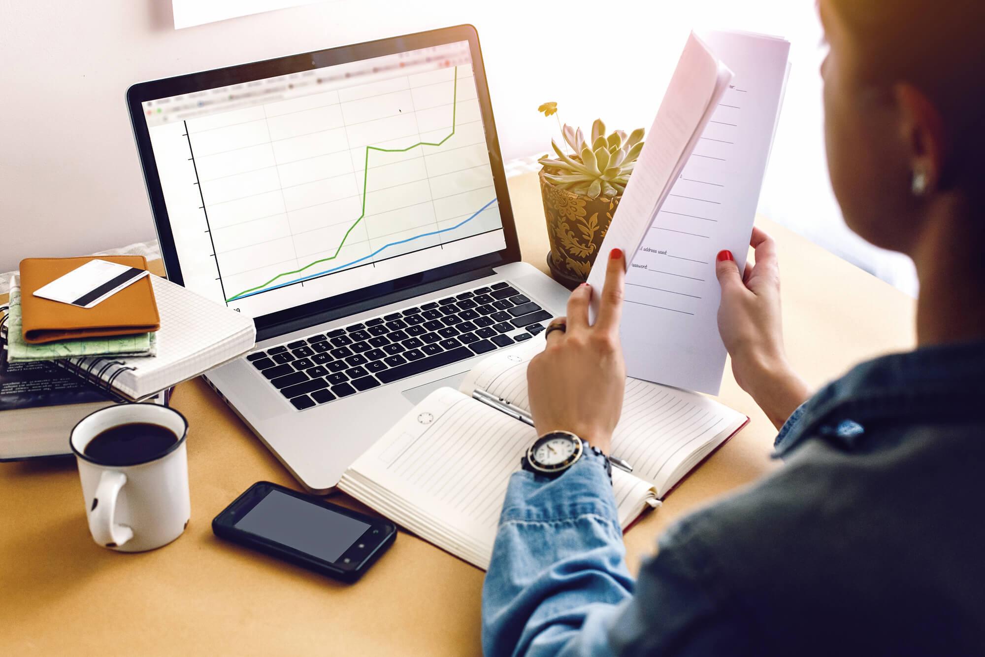 Mulher analisando gráficos contendo o valor justo no computador